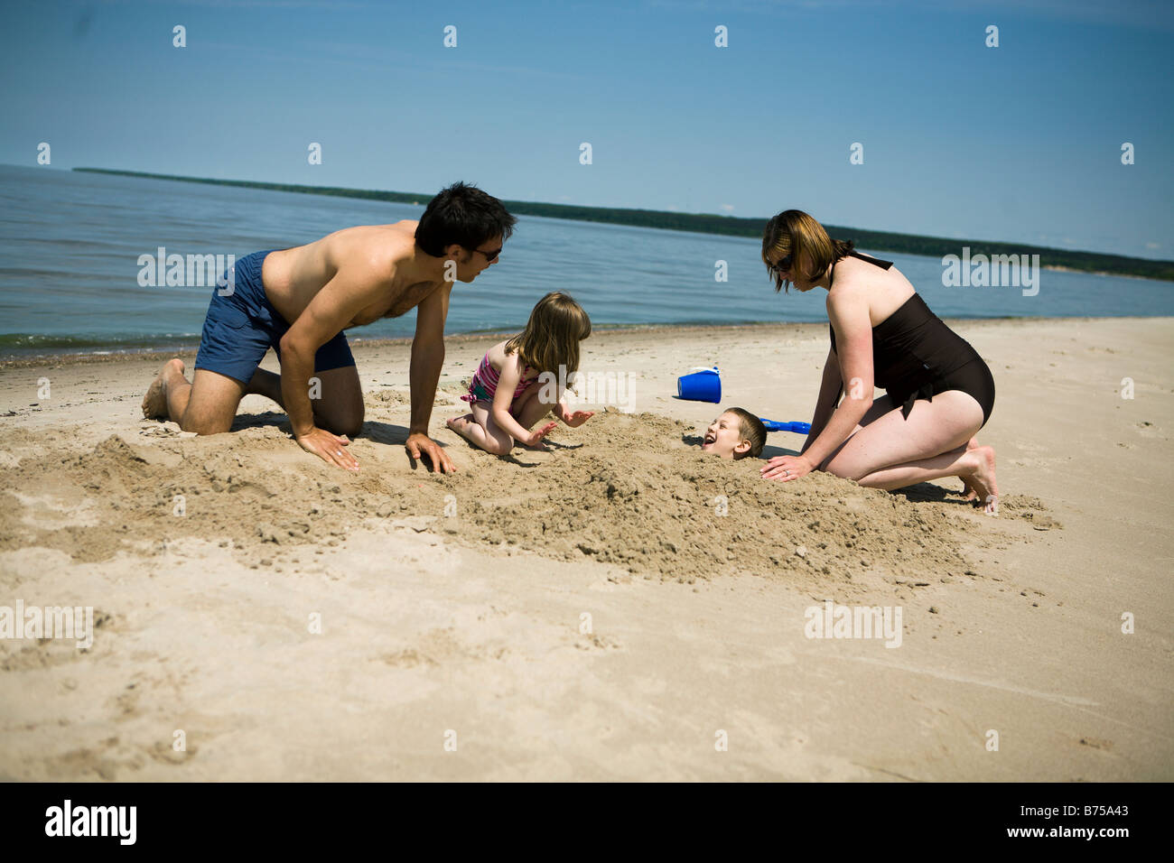Family in bathing suits burying boy in sand, Grand Beach provincial Park, Manitoba, Canada Stock Photo