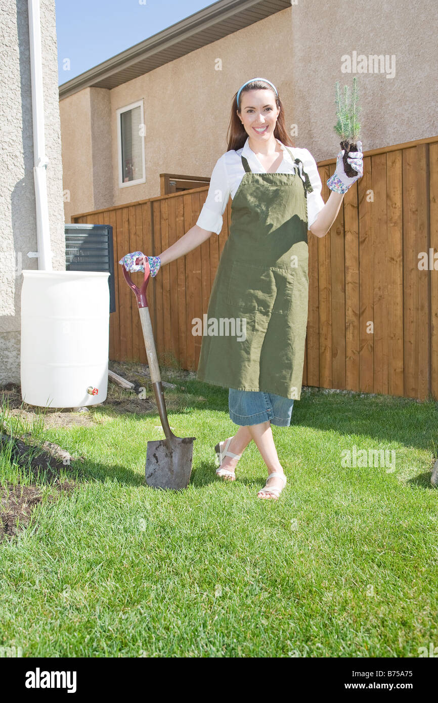 Woman holding tree seedling in front of rain barrel, Winnipeg, Manitoba, Canada - Stock Image