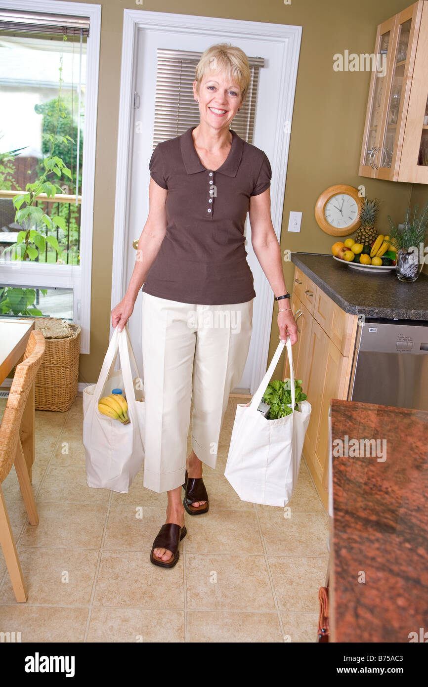 Senior woman carrying groceries in cloth bags, Winnipeg, Manitoba, Canada - Stock Image