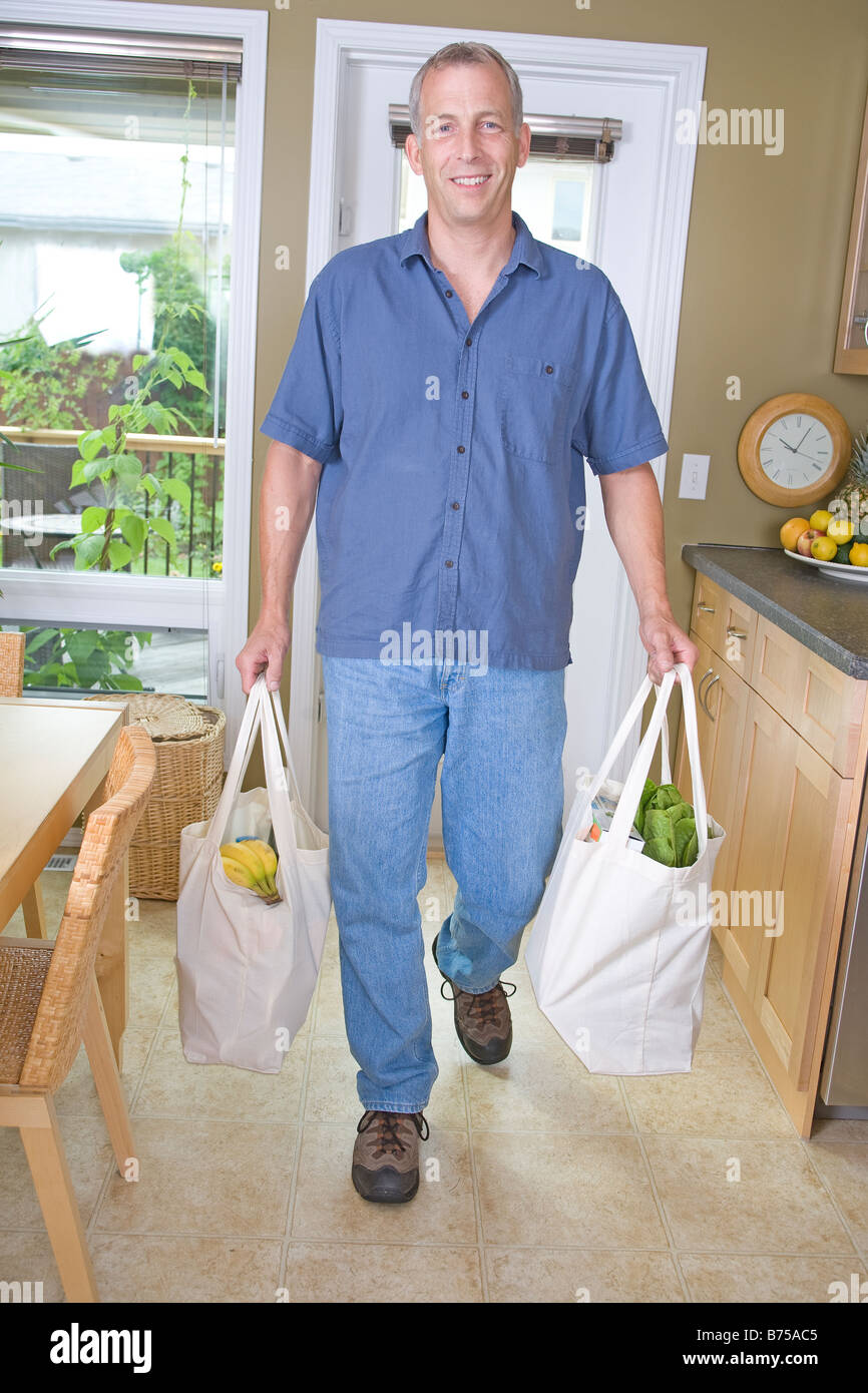 Senior man carrying groceries in cloth bags, Winnipeg, Manitoba, Canada - Stock Image