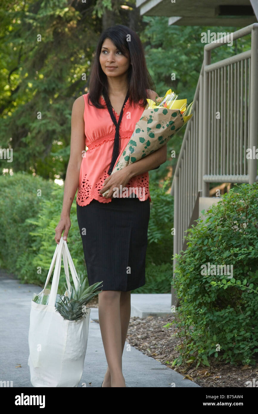 Young woman carrying groceries in cloth bags, Winnipeg, Manitoba, Canada - Stock Image