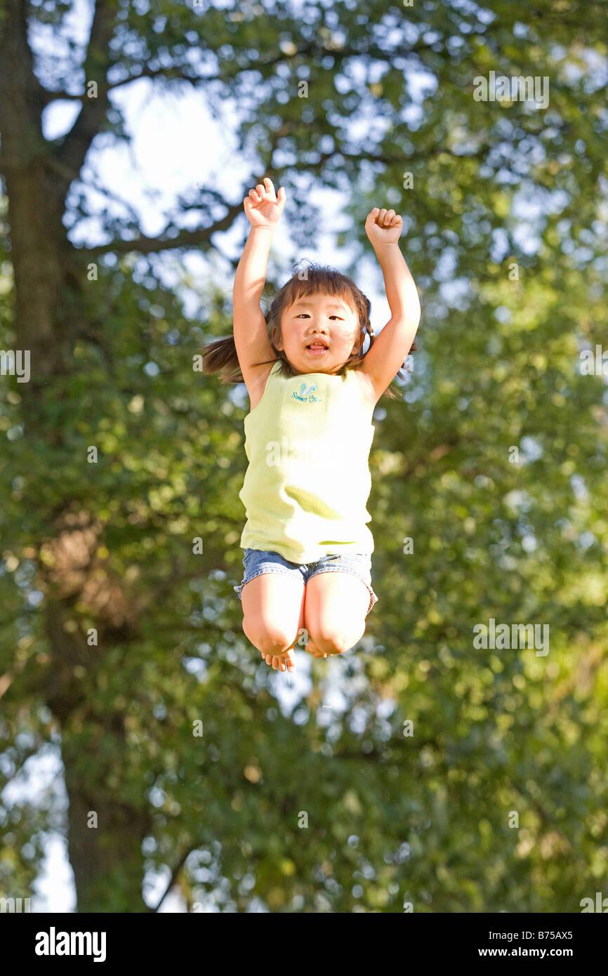 6 year old Asian girl jumping, Winnipeg, Manitoba, Canada - Stock Image