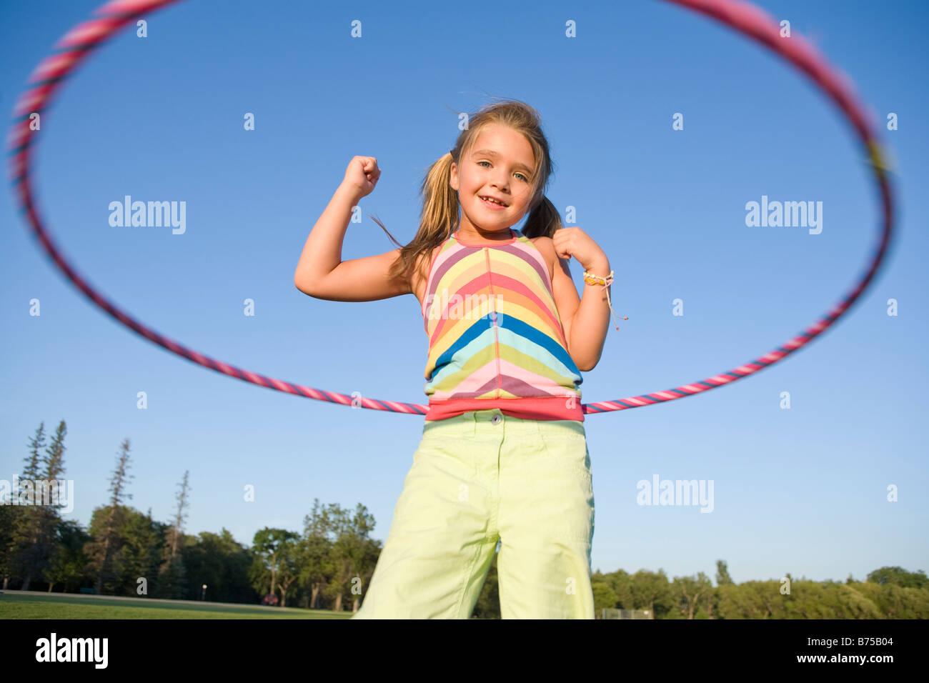 6 year old girl playing with hula hoop, Winnipeg, Manitoba, Canada - Stock Image