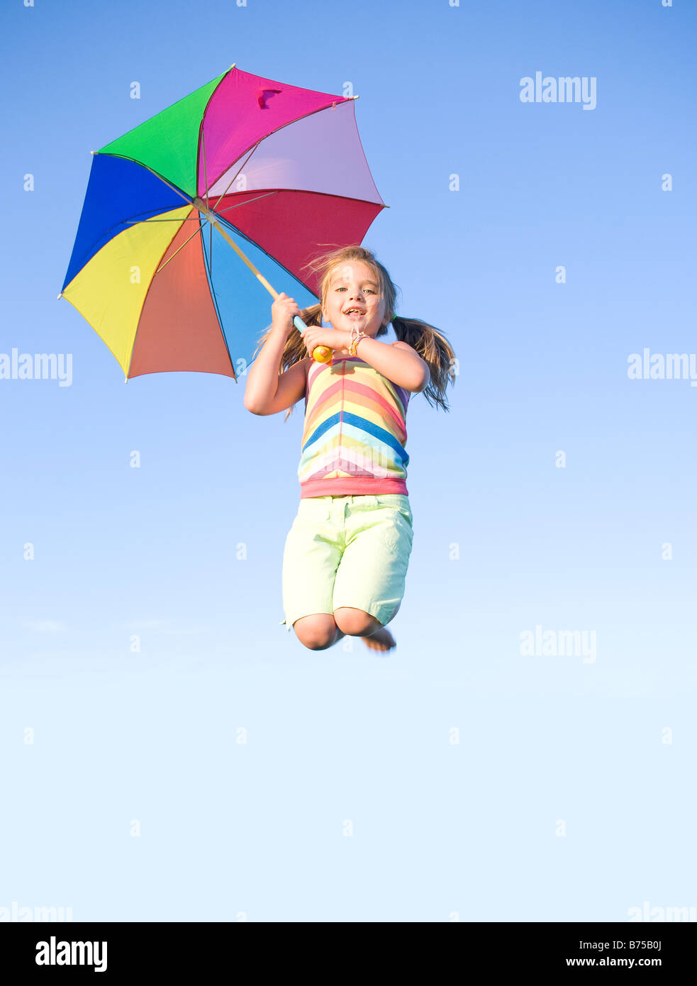Six year old girl jumping with umbrella, Winnipeg, Manitoba, Canada - Stock Image
