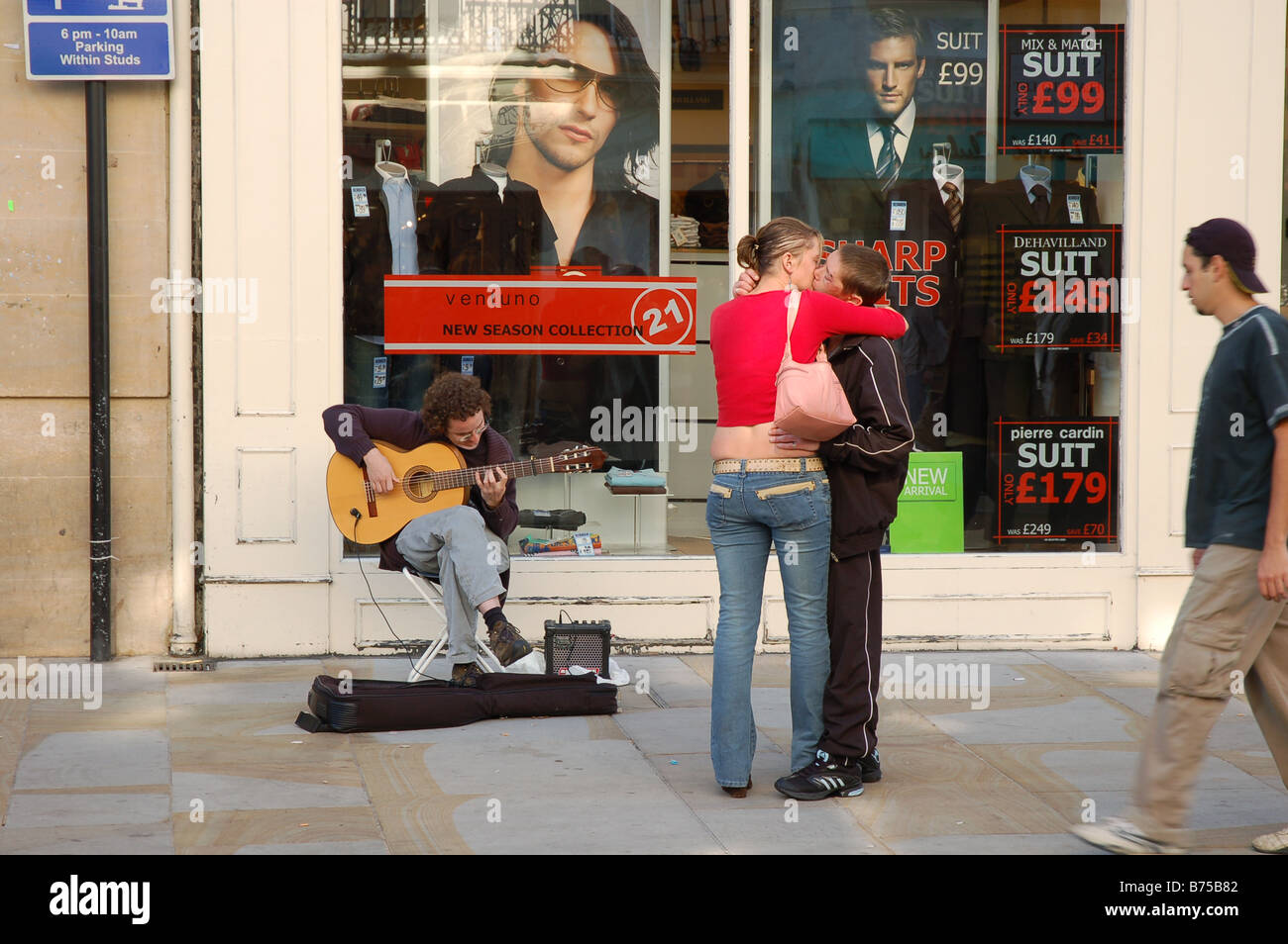 A young couple snogging in one of the main streets of Oxford city centre next to a busker playing classical guitar. - Stock Image