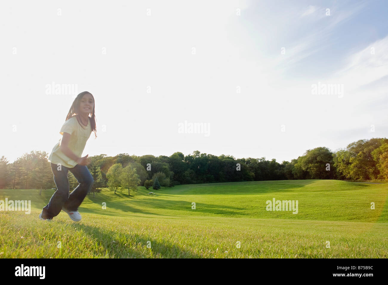 Eight year old girl running in park, Winnipeg, Canada - Stock Image