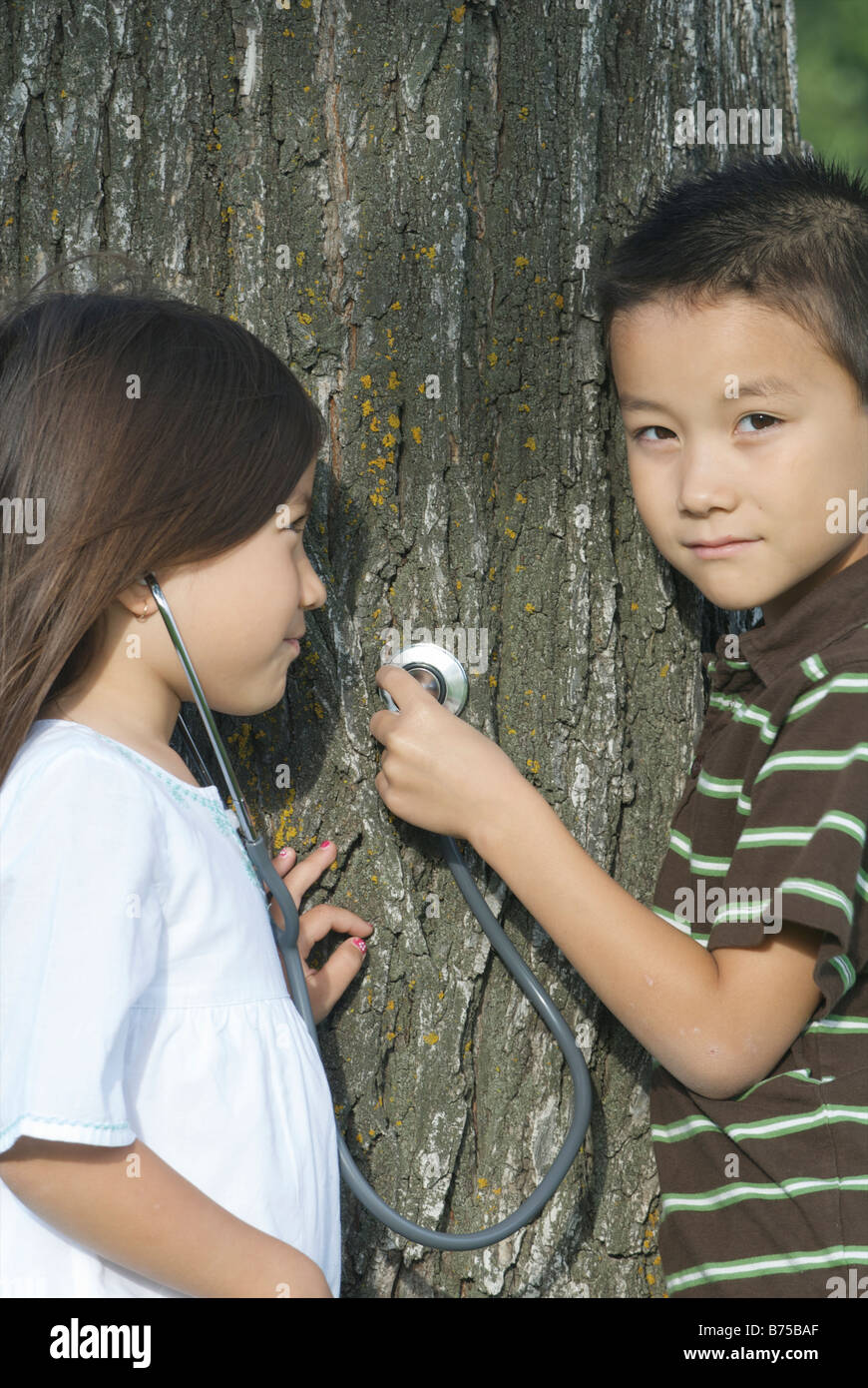 Five year old sister and seven year old brother with stethescope on tree, Winnipeg, Canada Stock Photo