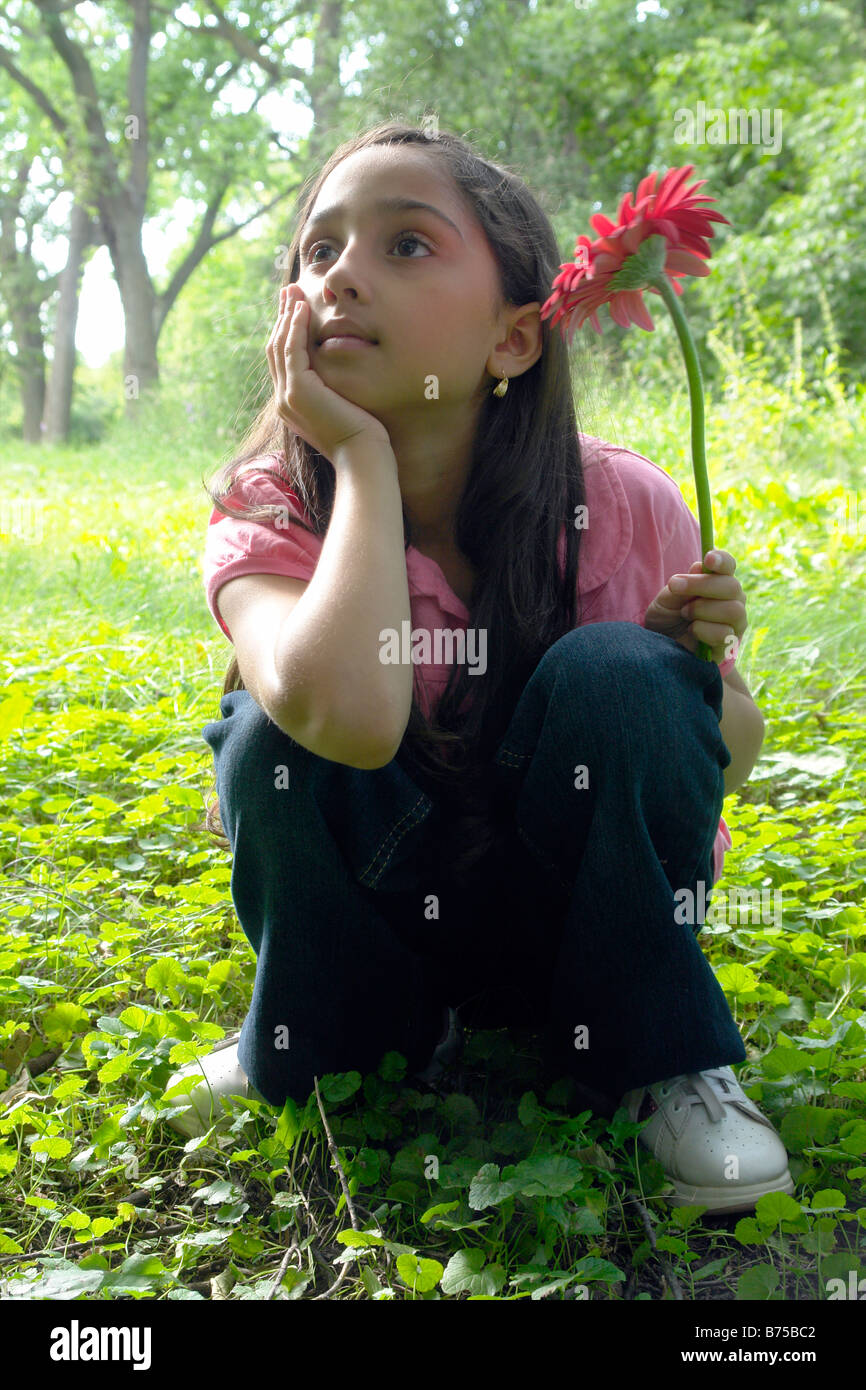 Eight year old girl in clearing with flower, Winnipeg, Canada - Stock Image
