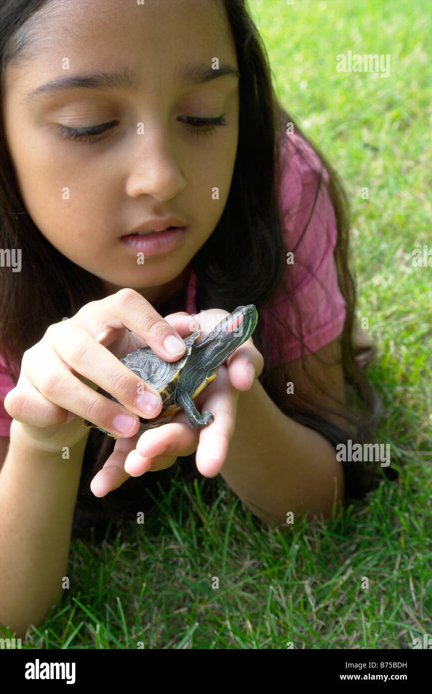 Eight year old girl lying in grass with turtle, Winnipeg, Canada - Stock Image