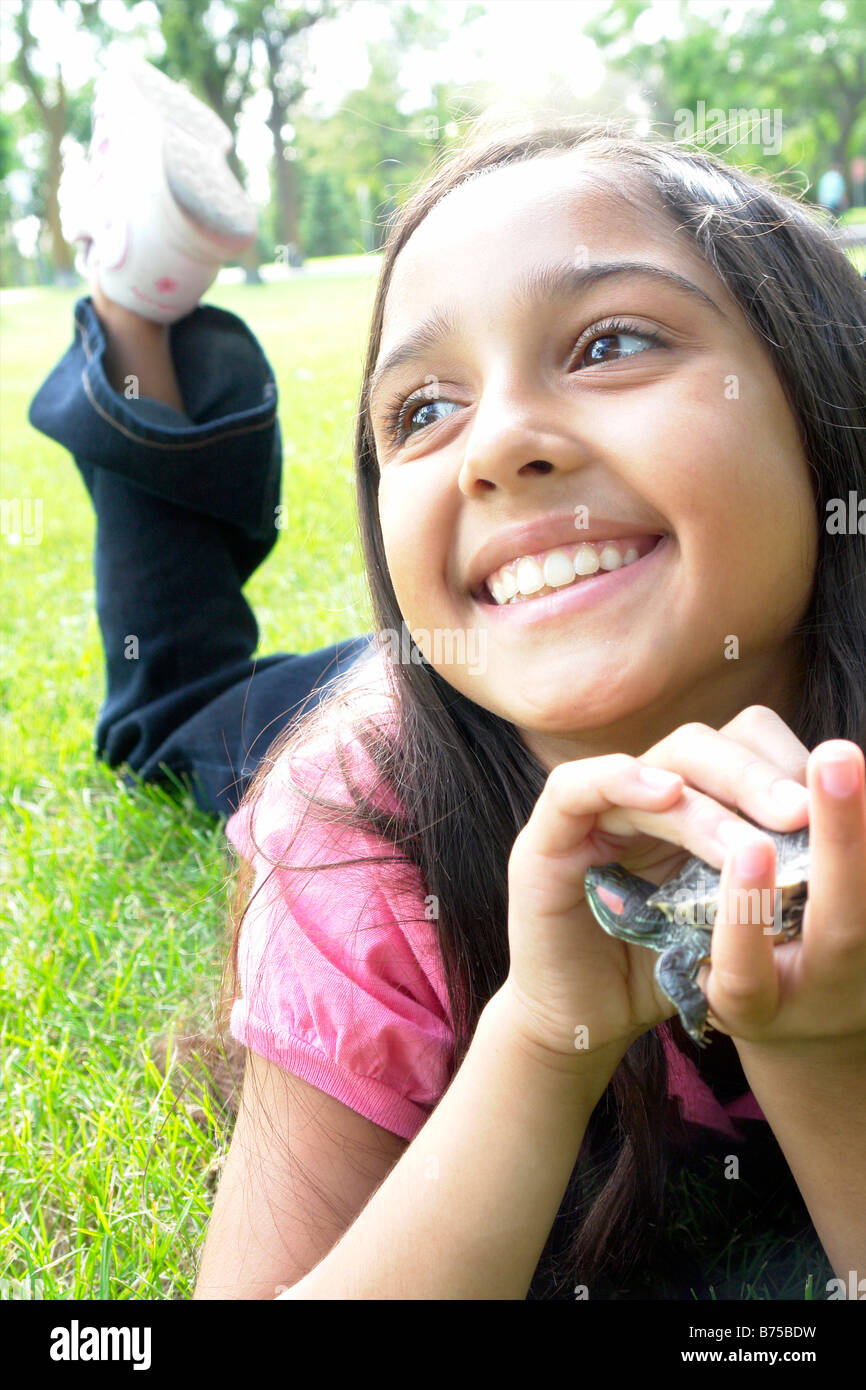 Smiling eight year old girl lying in grass with turtle, Winnipeg, Canada - Stock Image