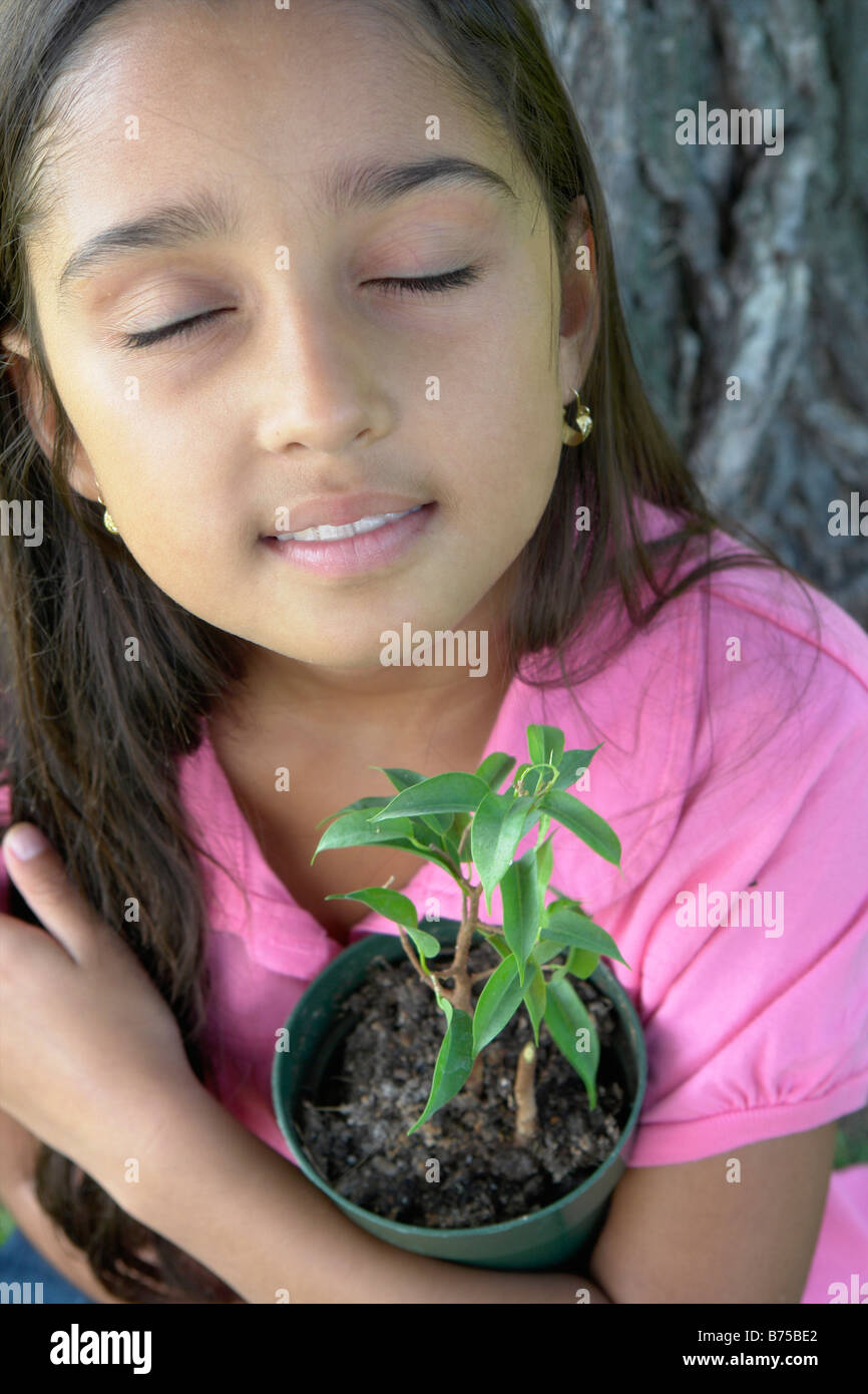 Eight year old girl with closed eyes holding small tree beside large tree, Winnipeg, Canada Stock Photo