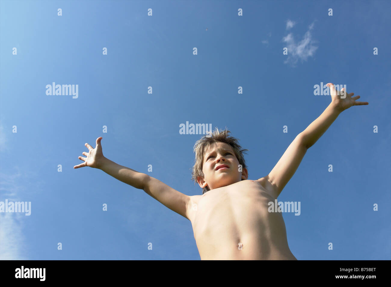 Eight year old boy with arms outstretched, Winnipeg, Canada - Stock Image