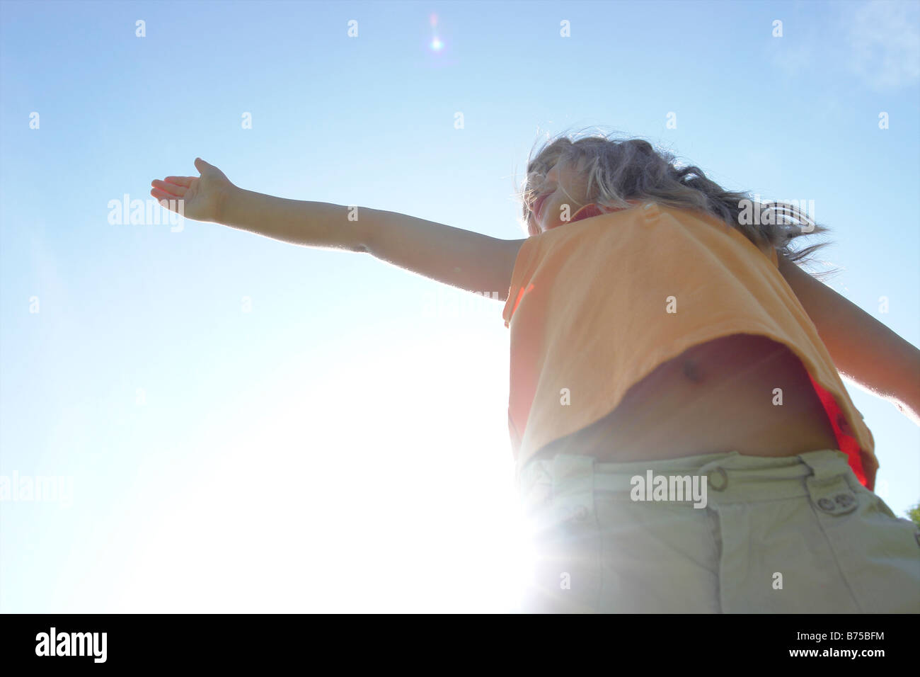 Sunflare, six year old girl with arms outstretched, Winnipeg, Canada - Stock Image
