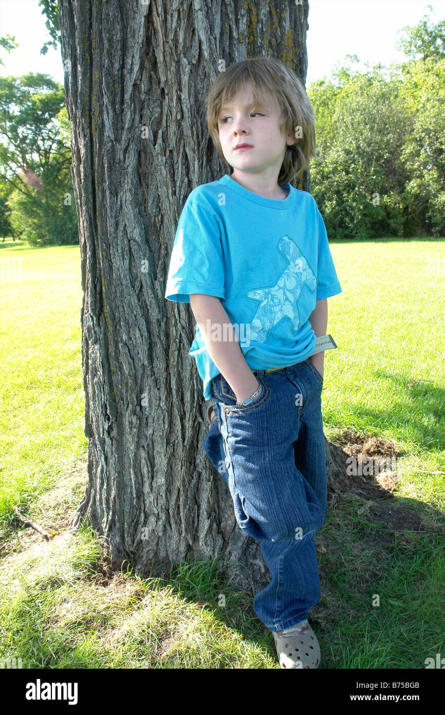 Six year old boy with hands in pockets stands beside tree, Winnipeg, Canada Stock Photo