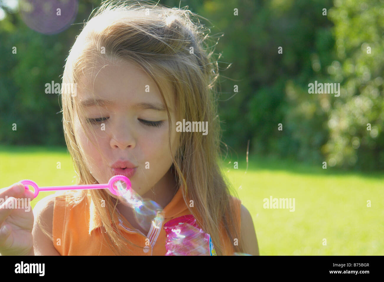 Six year old girl blowing bubbles in park, Winnipeg, Canada - Stock Image