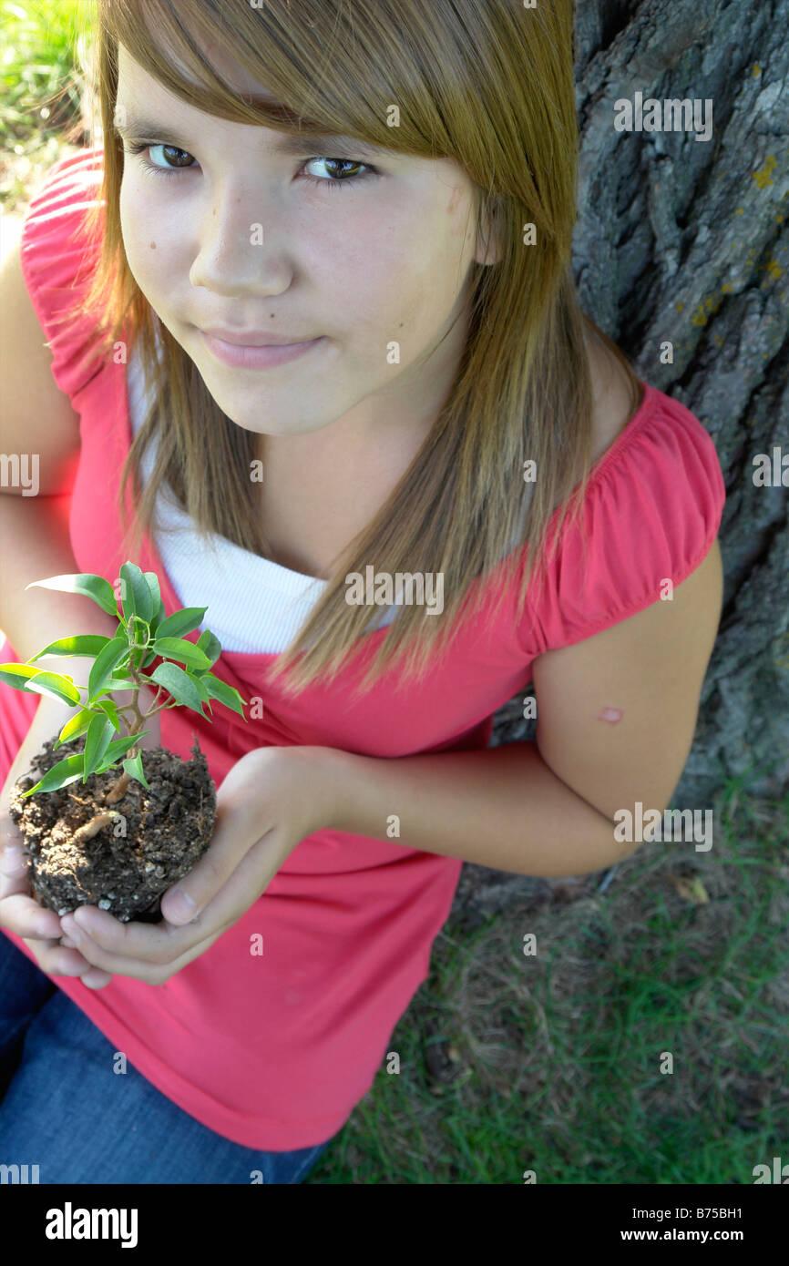 Thirteen year old girl seated beside tree holding small tree, Winnipeg, Canada - Stock Image