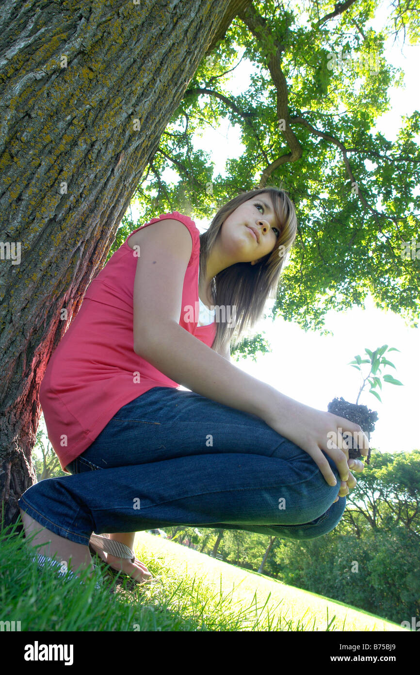 Thirteen year old girl holding small tree squatting beside larger tree, Winnipeg, Canada - Stock Image