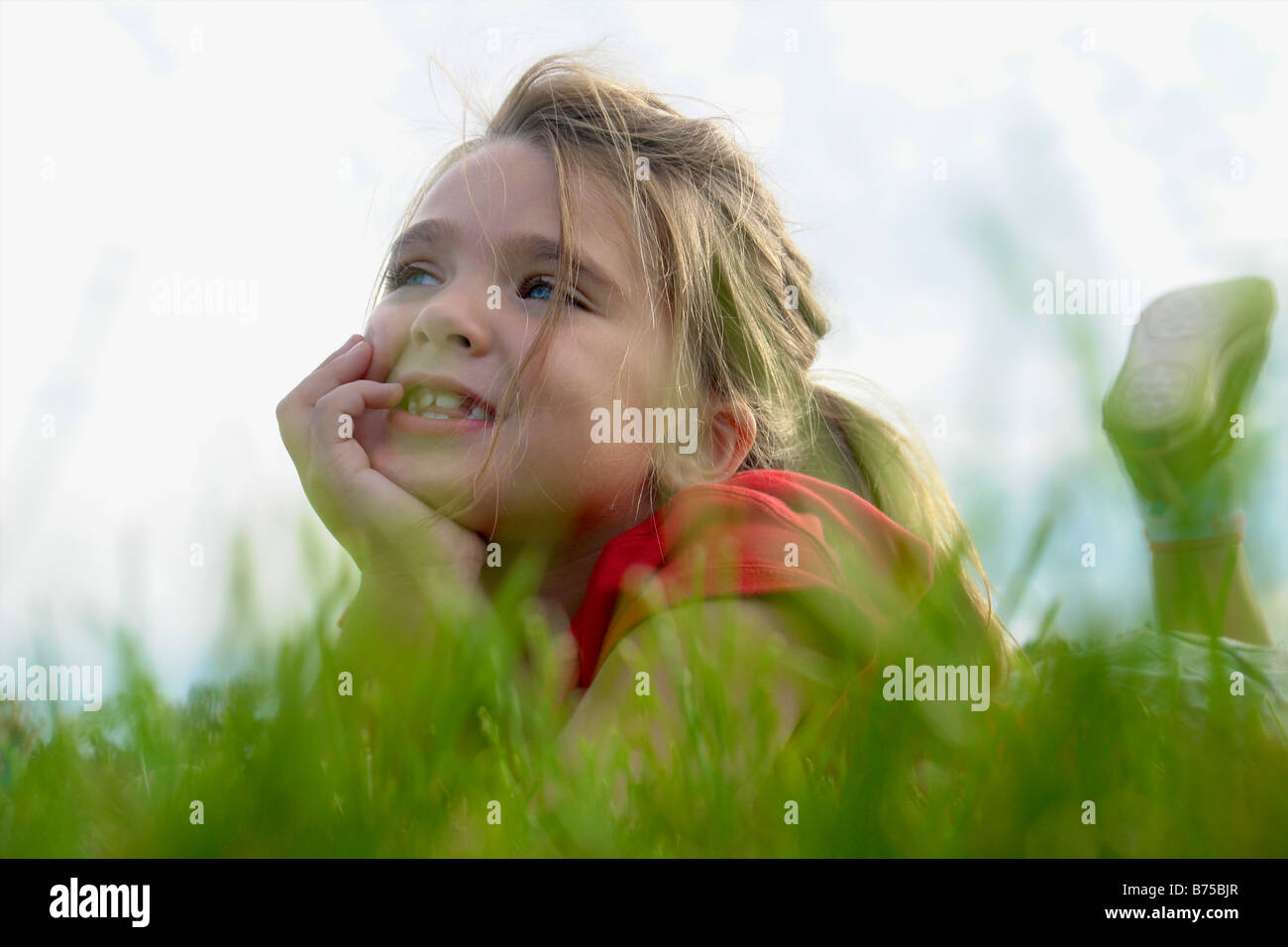 Six year old girl with chin in hands lying on grass, Winnipeg, Canada - Stock Image