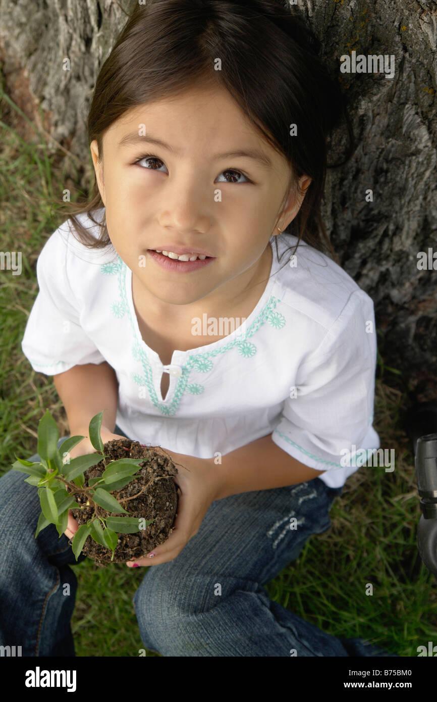 Six year old girl holding small tree, looking upward, Winnipeg, Canada - Stock Image