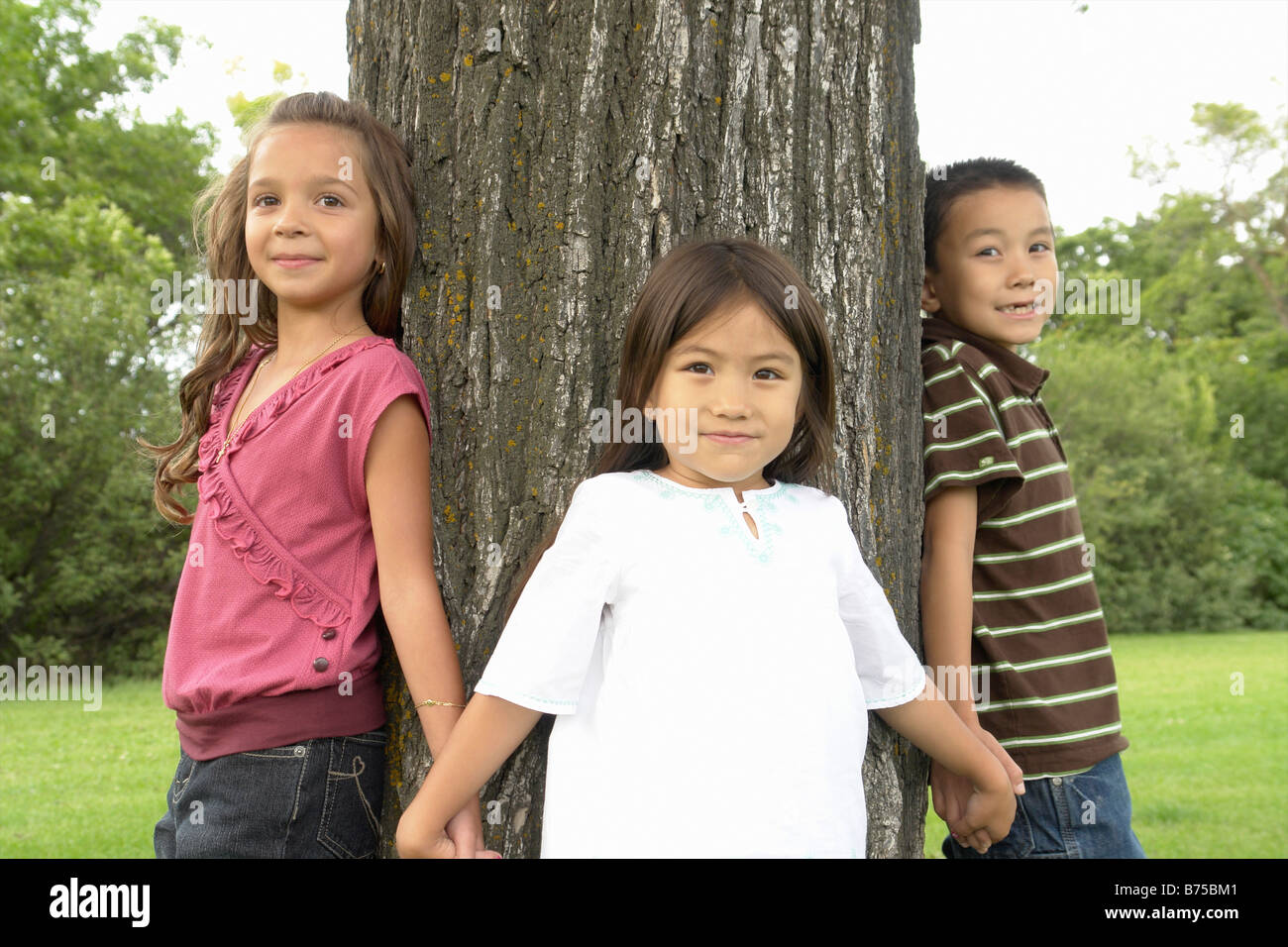 Seven and five year old girls and seven year old boy hold hands around tree, Winnipeg, Canada - Stock Image
