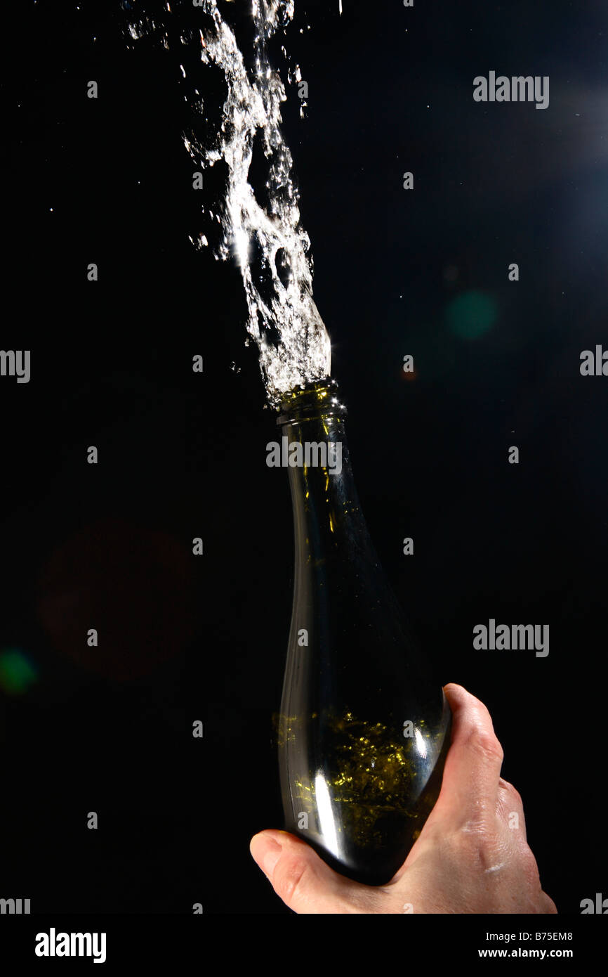 Champagne bursting from a bottle on black background. - Stock Image