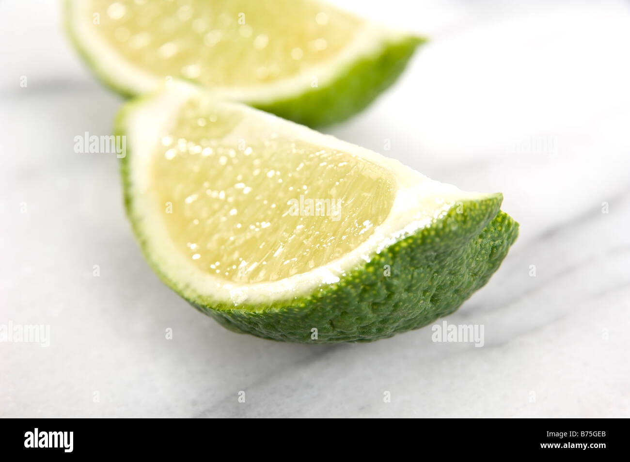 Close up of two slices of lime placed on a marble background. The front slice is drippingly juicy and pin sharp. - Stock Image