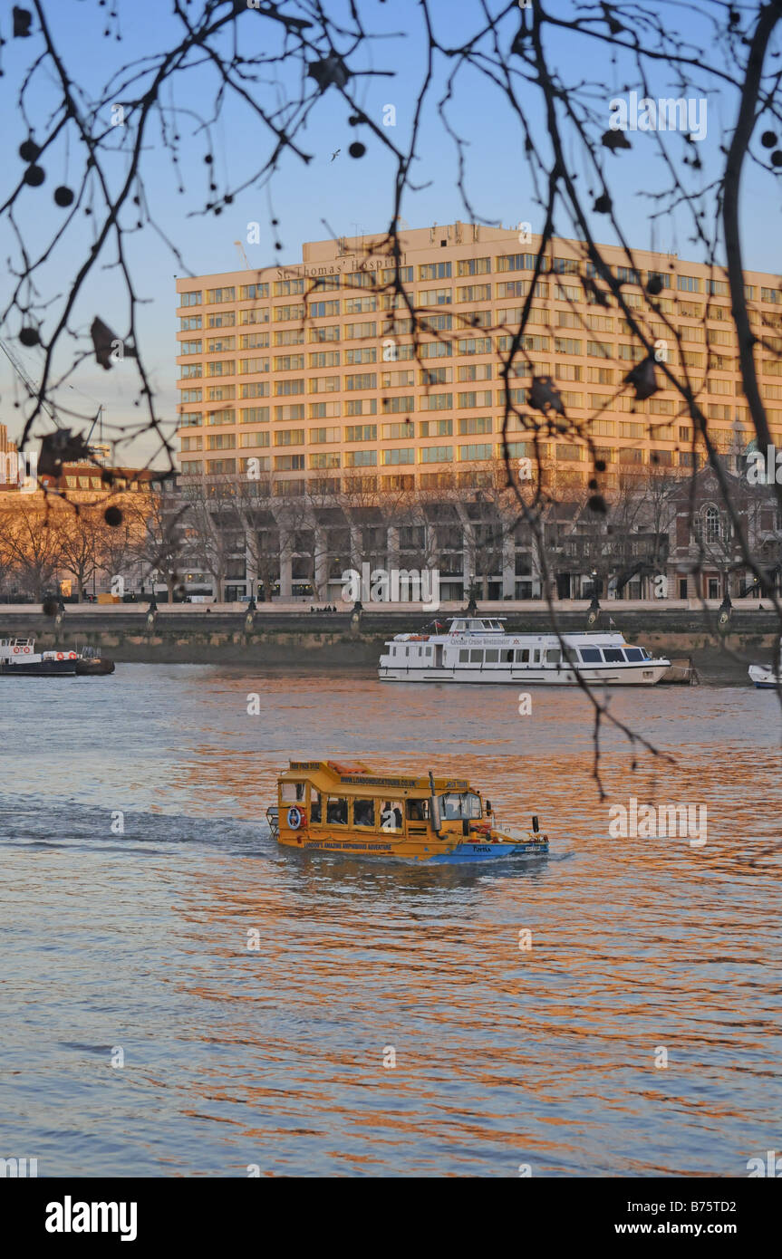 Yellow amphibious DUKW (Duck) from London Duck Tours in the Thames in foreground with St Thomas' Hospital in - Stock Image