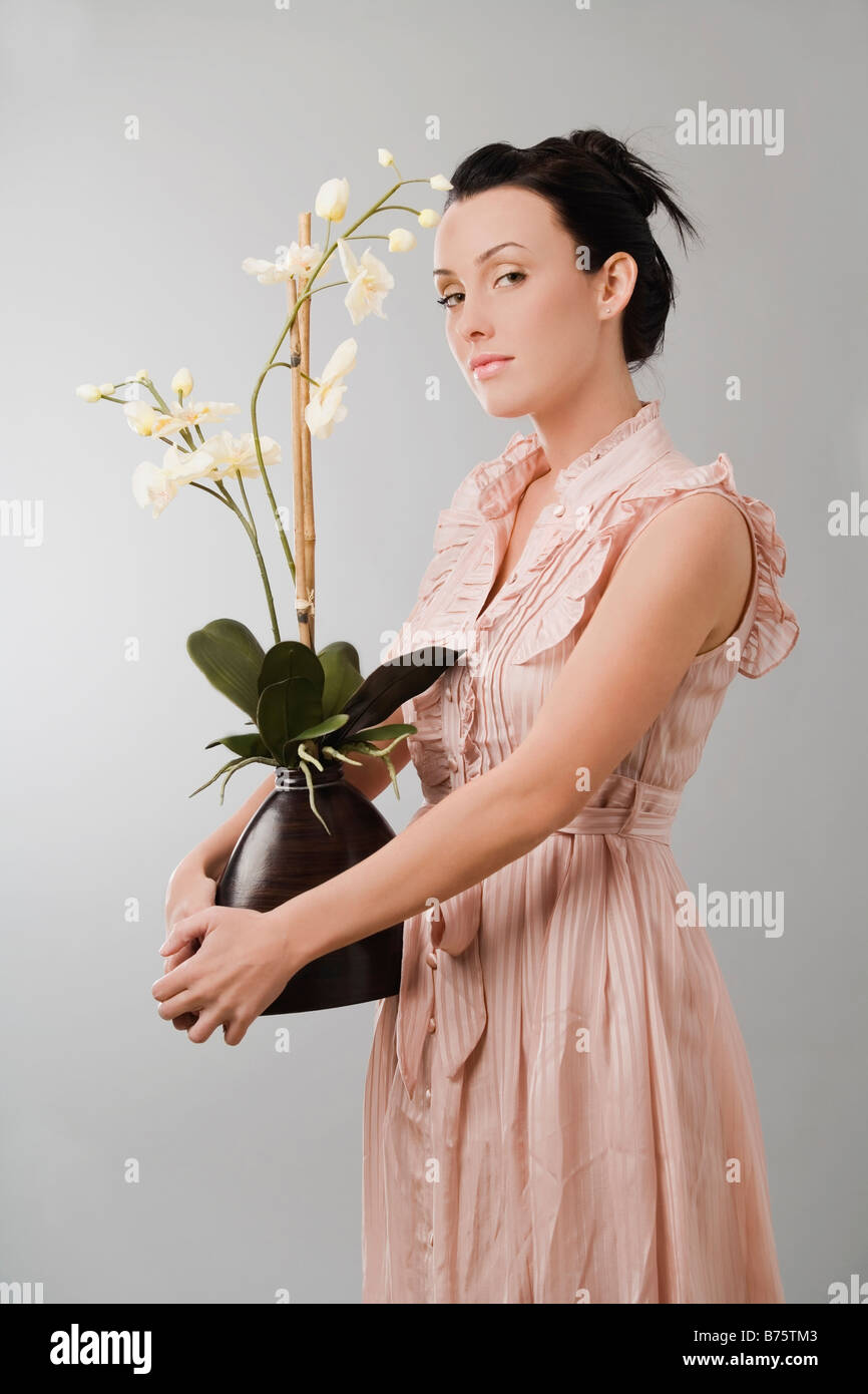 Portrait Of A Young Woman Holding A Flower Pot Stock Photo