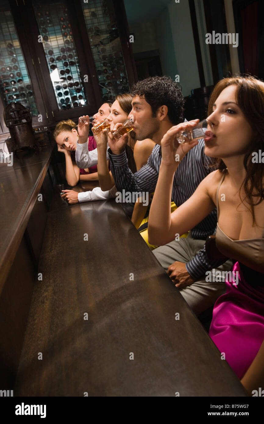 Five friends sitting at a bar counter and drinking whiskey - Stock Image