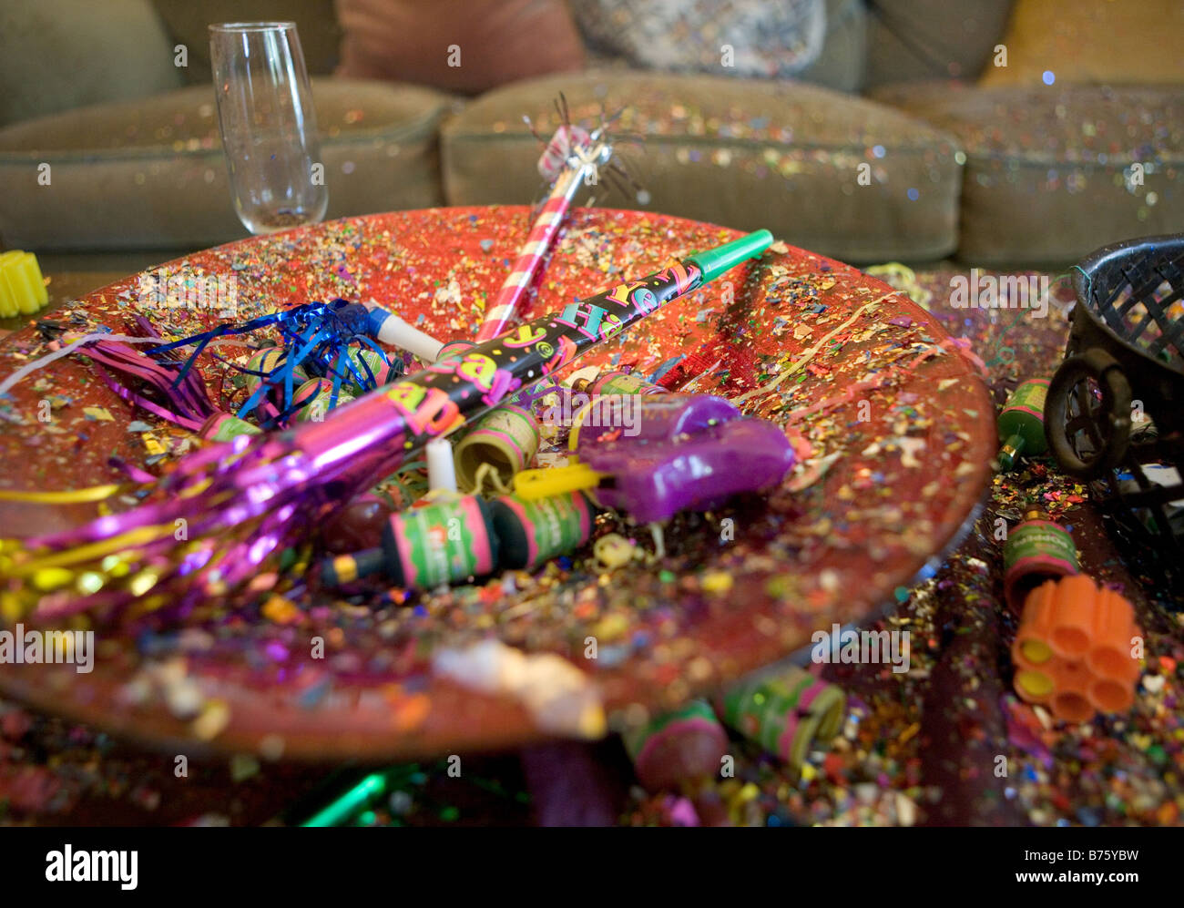 New Years Eve Party Wreckage including a champagne glass confetti poppers horns streamers and other noise makers - Stock Image