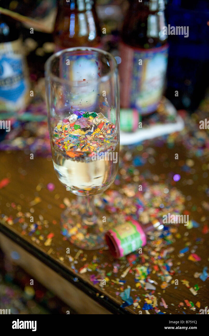 New Years Eve Party Wreckage including a champagne glass with confetti floating on the surface of the champagne - Stock Image