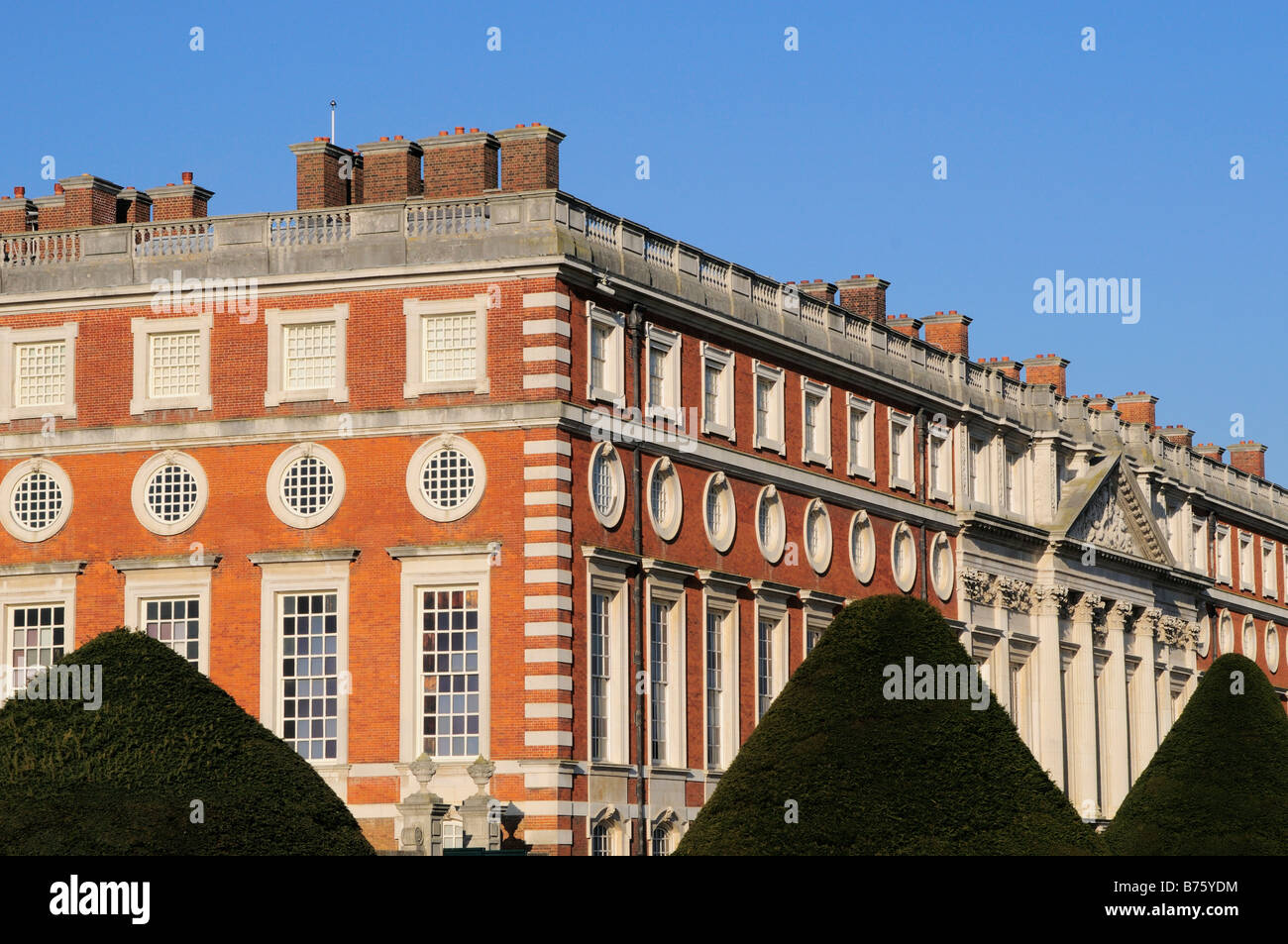 Hampton Court Palace and grounds with conically shaped yew trees Surrey - Stock Image