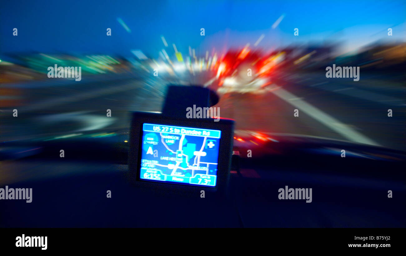 display of a GPS navigation system on car dashboard at night - Stock Image