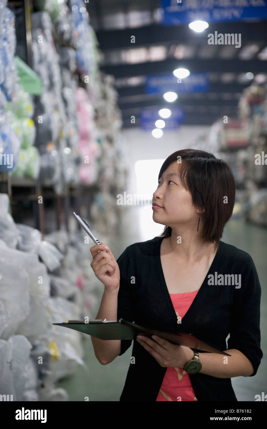 An employee at a warehouse doing an inventory check. - Stock Image