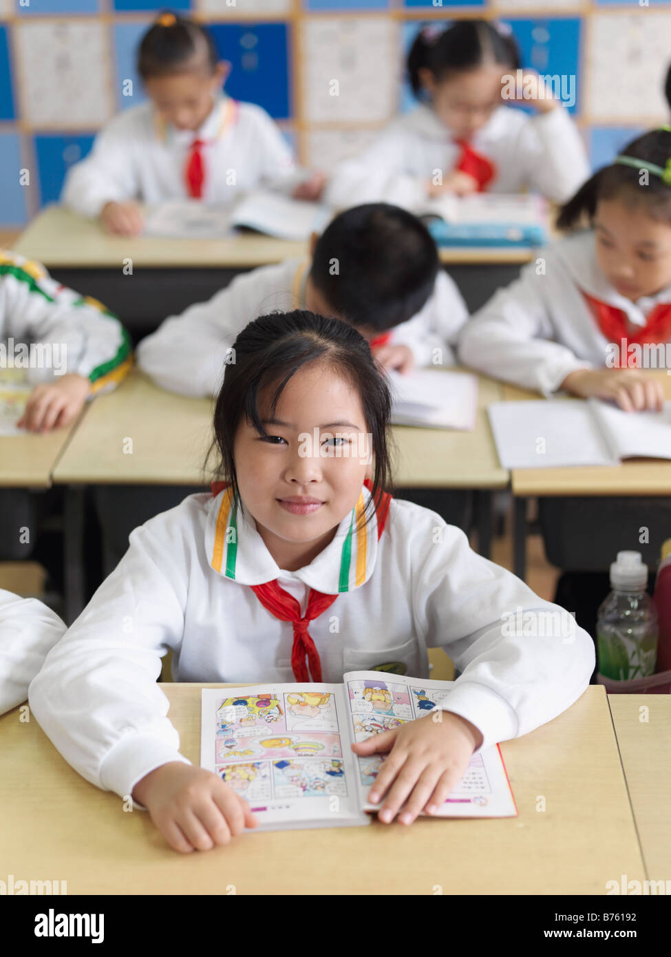A classroom of young Chinese students reading a lesson from their textbook. - Stock Image
