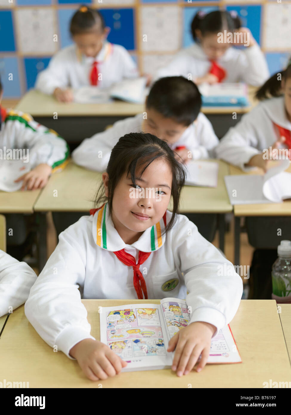 A classroom of young students reading a lesson from their textbook. - Stock Image