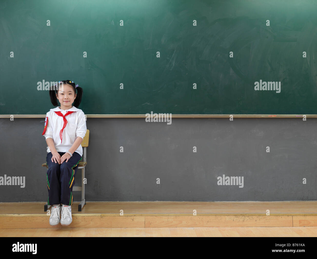 A portrait of a Chinese school girl sitting in front of a chalkboard. - Stock Image