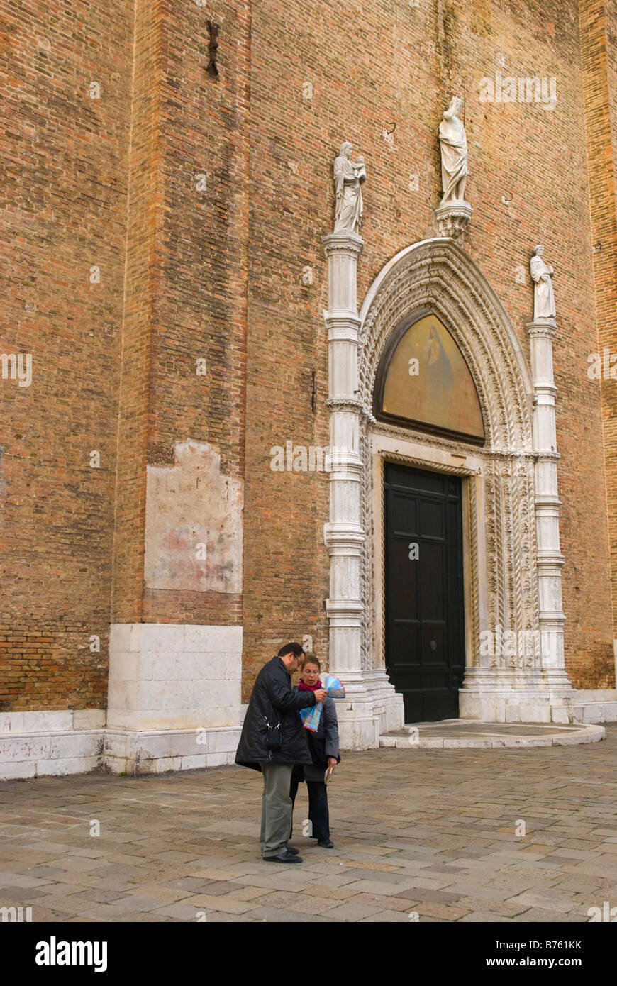 Couple reading a map at Campo San Rocco in Venice Italy Europe - Stock Image