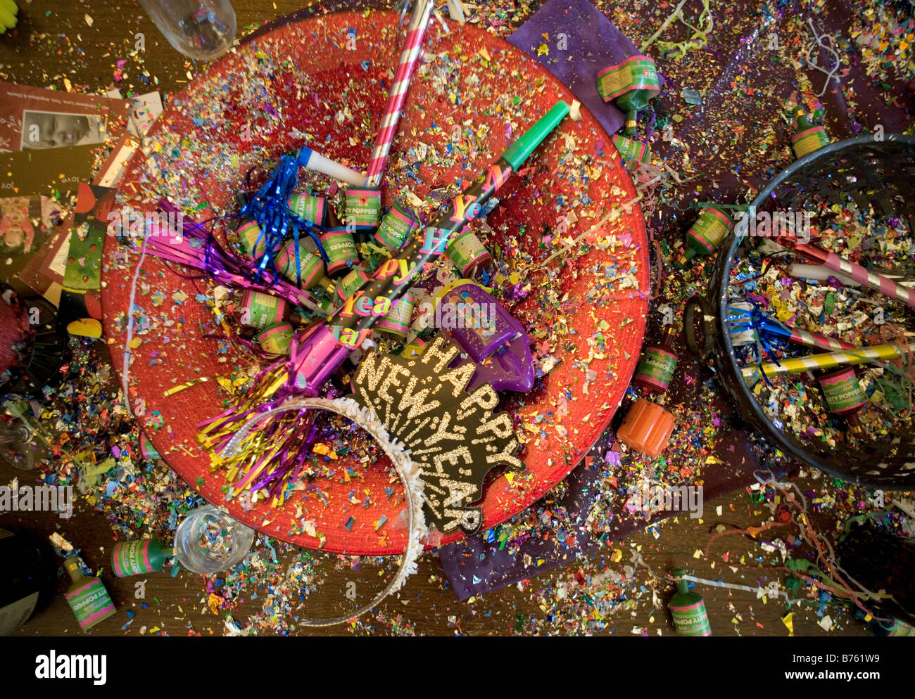 New Years Eve Party Wreckage including confetti poppers horns streamers noise makers champagne glasses and hats - Stock Image