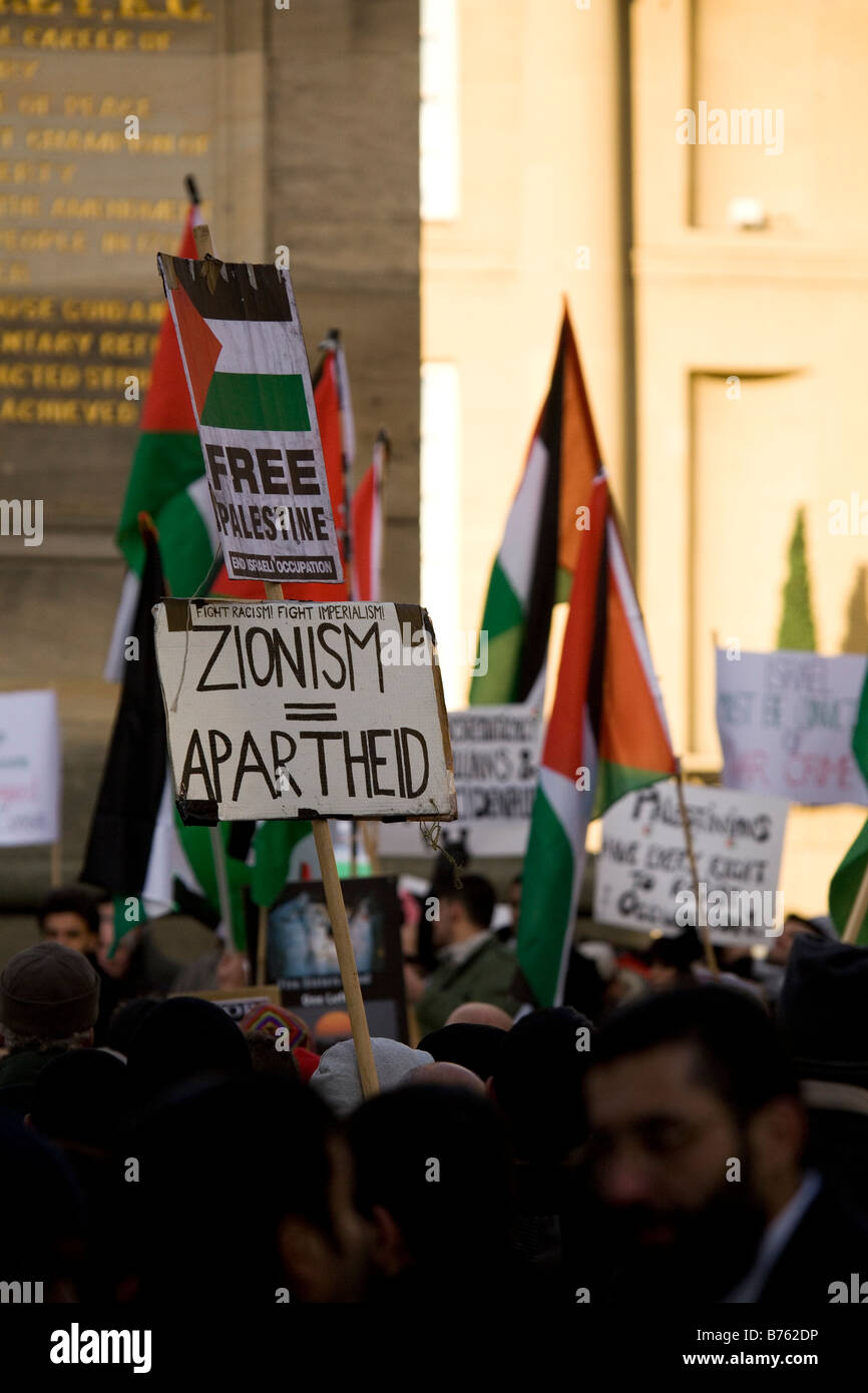 A placard at a demonstration in central Newcastle England compares Zionism to Apartheid. - Stock Image