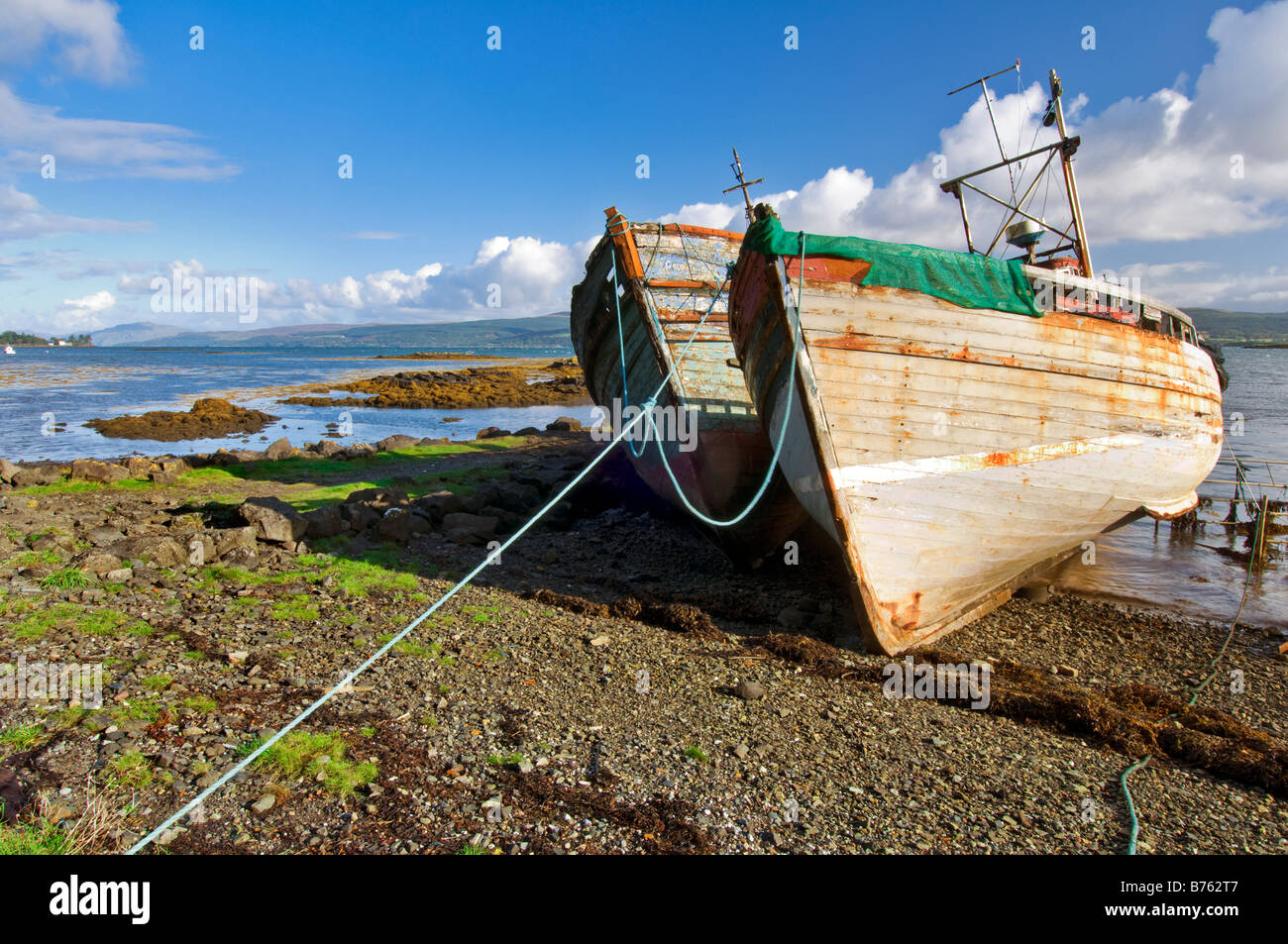 Abandoned and ruined fishing trawlers near Salen on the shoreline of the Sound of Mull, taken on a birght sunny - Stock Image