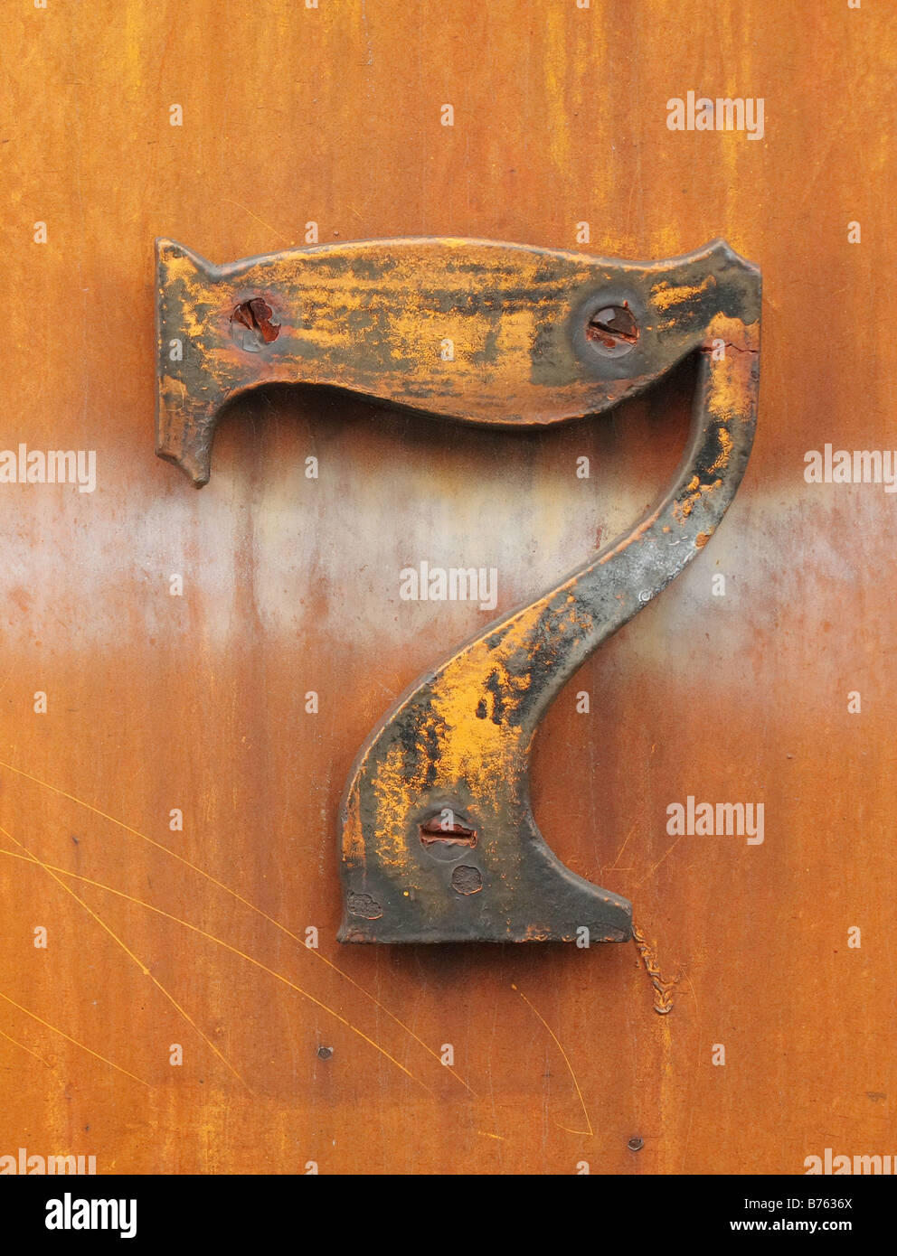 grungy number seven affixed to rusty industrial metal - Stock Image