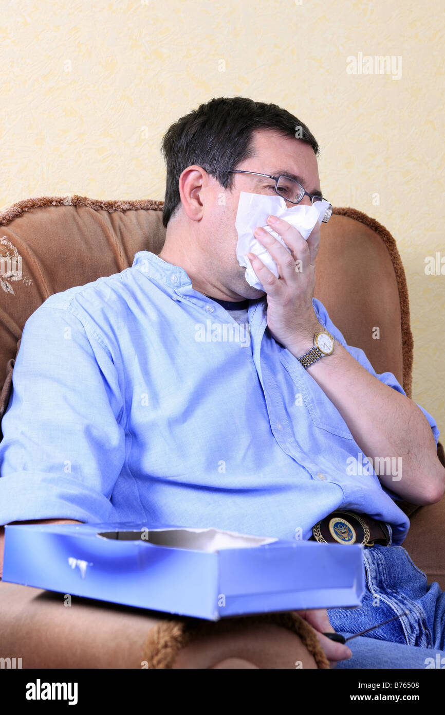 Adult male suffering with a flu virus seen here sneezing - Stock Image