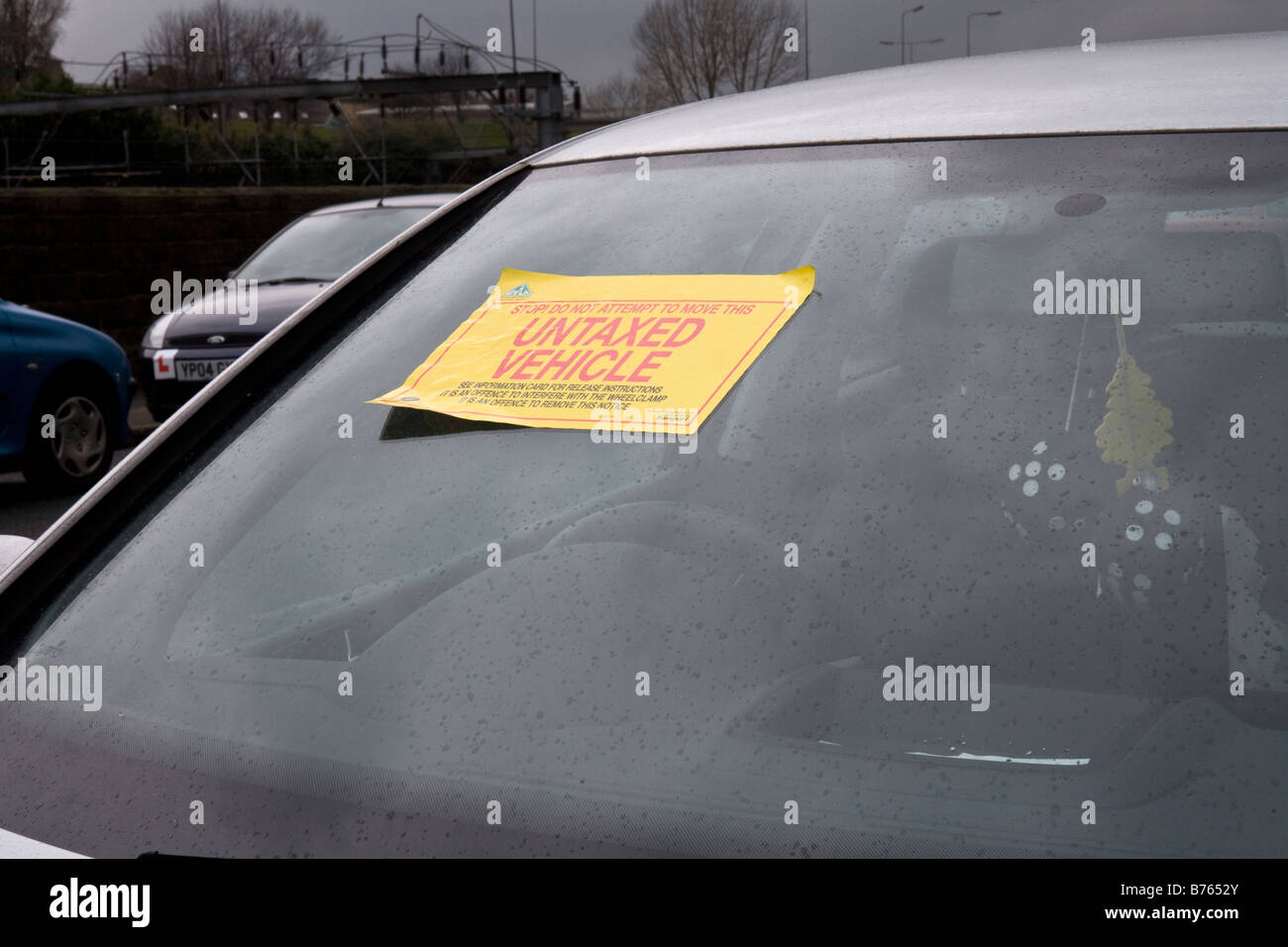 Untaxed Vehicle notice stuck on a car windscreen. Stock Photo
