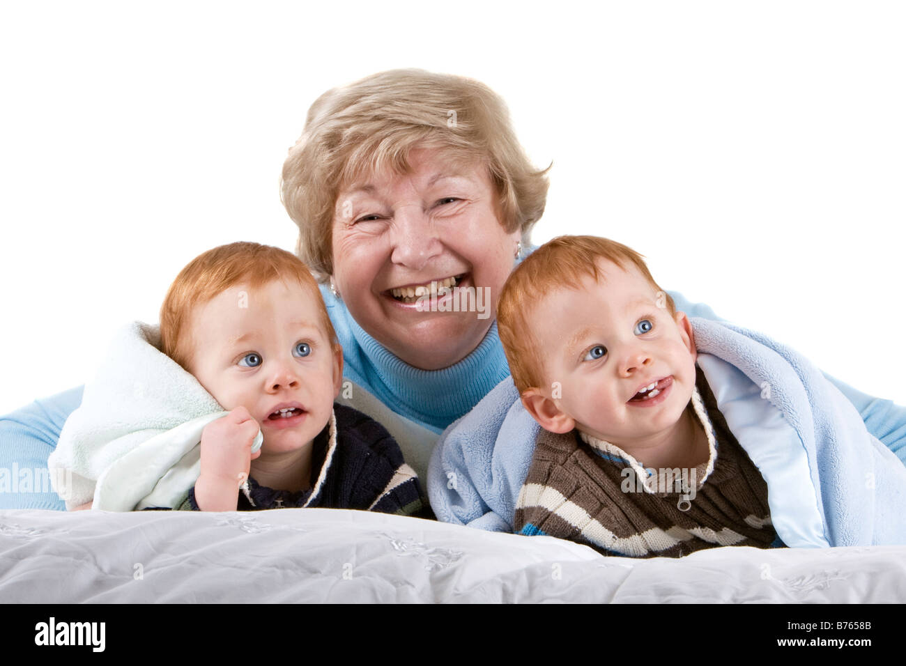 Happy grandmother with redheaded grandsons with blanket - Stock Image