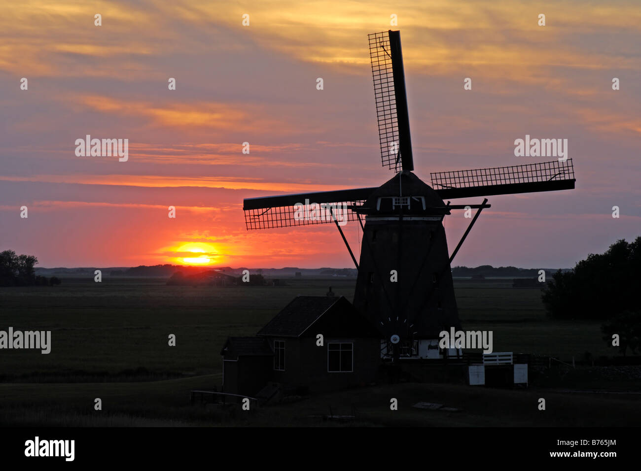 dutch windmill red sunset backlight holland texel island sillhouette afterglow evening mood - Stock Image