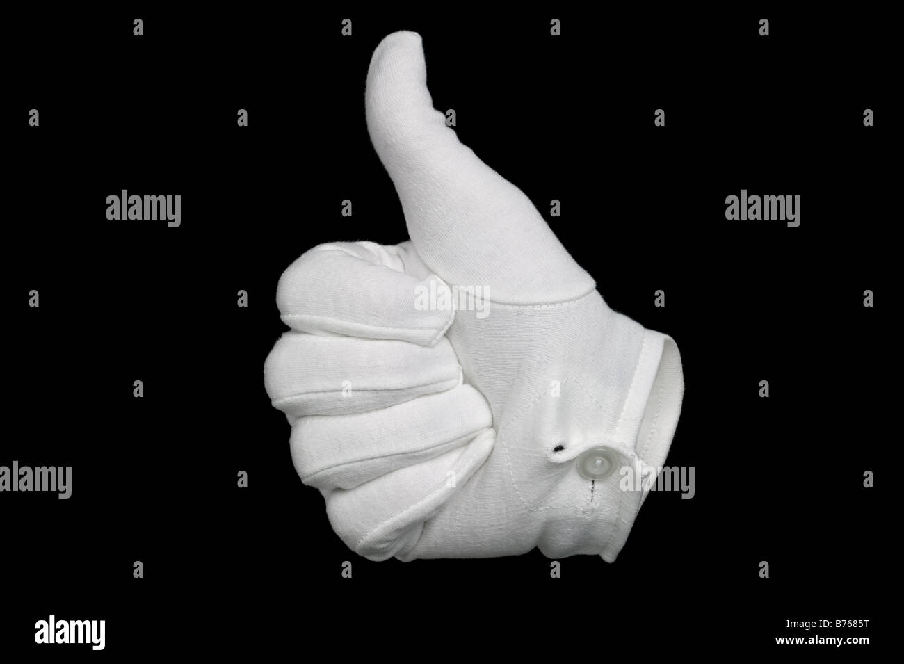 Hand in a white cotton glove gesturing a thumbs up sign isolated on a black background Invisible man effect on glove - Stock Image