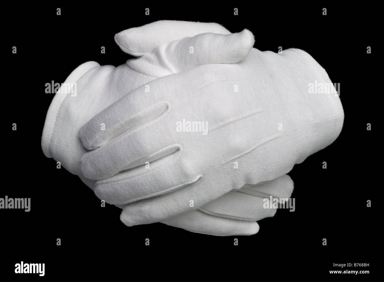 Hands held in white cotton gloves isolated on a black background - Stock Image
