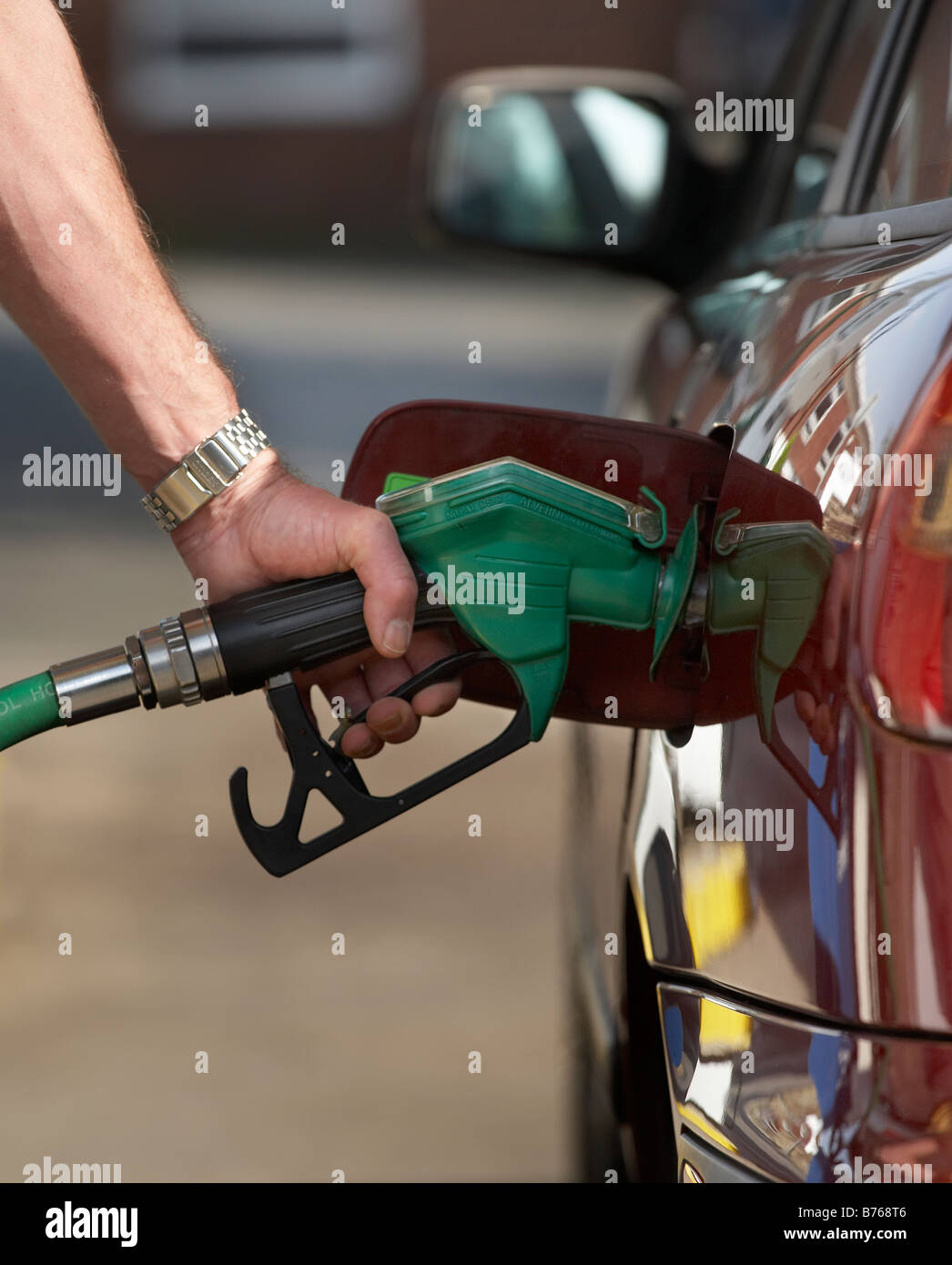 MAN FILLING CAR AUTOMOBILE GAS GASOLINE FUEL PETROL DIESEL TANK - Stock Image