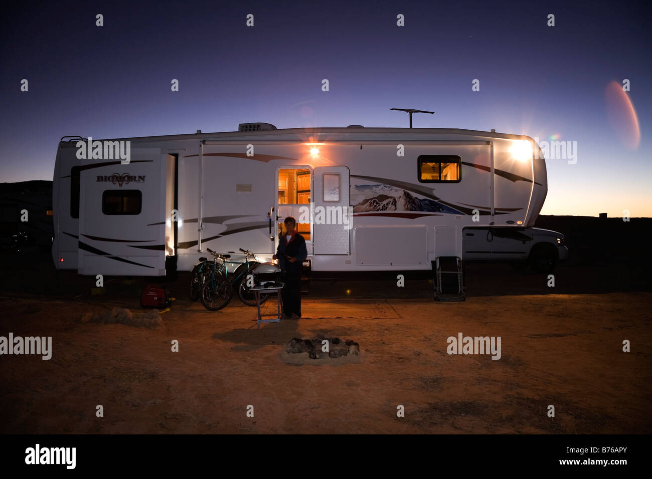 Woman cooking at night on BBQ outside a Fifth Wheel recreational vehicle camped on Lone Rock Beach Primitive Campground - Stock Image